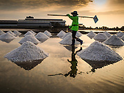09 MARCH 2015 - NA KHOK, SAMUT SAKHON, THAILAND:  A worker walks out of a salt pond after raking sea salt into mounds during the salt harvest in Samut Sakhon. The coastal provinces of Samut Sakhon and Samut Songkhram, about 60 miles from Bangkok, are the center of Thailand's sea salt industry. Salt farmers harvest salt from the waters of the Gulf of Siam by flooding fields and then letting them dry through evaporation, leaving a crust of salt behind. Salt is harvested through dry season, usually February to April. The 2014 salt harvest went well into May because the dry season lasted longer than normal. Last year's harvest resulted in a surplus of salt, driving prices down. Some warehouses are still storing salt from last year. It's been very dry so far this year and the 2015 harvest is running ahead of last year's bumper crop. One salt farmer said prices are down about 15 percent from last year.   PHOTO BY JACK KURTZ