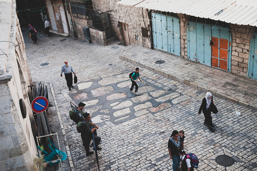 Jerusalem - October 20, 2010: Outside the Third Station of the Cross on the Via Dolorosa in Jerusalem's Muslim Quarter, a Palestinian boy runs across several large two-thousand-year-old paving stones. The stones were discovered 10 feet below the present street level in 1980.