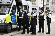 Metropolitan Police officers wearing face coverings prepare to speak to environmental activists from Extinction Rebellion protesting outside the Shell Centre on the 25th anniversary of the killings of the Ogoni Nine on 10 November 2020 in London, United Kingdom. The Ogoni Nine, leaders of the Movement for the Survival of the Ogoni People (MOSOP) including activist Ken Saro-Wiwa, were executed by the Nigerian government in 1995 after having led a series of peaceful marches involving an estimated 300,000 Ogoni people against the environmental degradation of the land and waters of Ogoniland by Shell and to demand both a share of oil revenue and greater political autonomy.