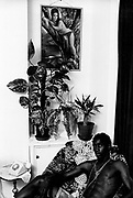 Youth sitting beneath portrait of partially naked woman. Photo by Richard Saunders 1983