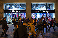 Pedestrians walk at night past a Disney Store on the famous Champs Elysees boulevard.