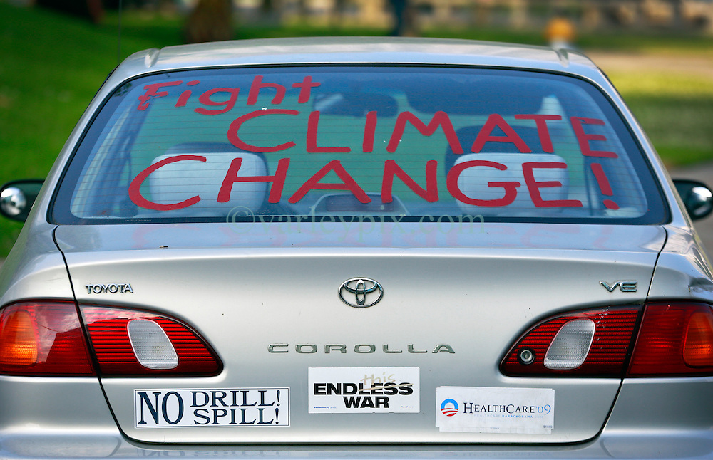 22 April 2014. New Orleans, Louisiana. <br /> A protester's car parked near a small group of protesters with Global Climate Convergence at a rally outside city hall on Earth Day to promote awareness for their cause for 'People - Planet - Peace over Profit.'<br /> Photo; Charlie Varley/varleypix.com