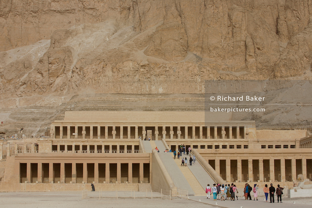 "Tourists approach the ancient Egyptian Temple of Hatshepsut near the Valley of the Kings, Luxor, Nile Valley, Egypt. The Mortuary Temple of Queen Hatshepsut, the Djeser-Djeseru, is located beneath cliffs at Deir el Bahari (""the Northern Monastery""). The mortuary temple is dedicated to the sun god Amon-Ra and is considered one of the ""incomparable monuments of ancient Egypt."" The temple was the site of the massacre of 62 people, mostly tourists, by Islamists on 17 November 1997."
