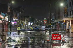 © Licensed to London News Pictures. 15/01/2020. Slough, UK. Police maintain a cordon as a van sits under a huge section of metal roof on the High Street in Slough after winds from storm Brendon tore it from the top of a building. Photo credit: Peter Manning/LNP