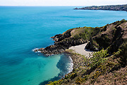 Vicard harbour, a tiny hidden cove on the North Coast of Jersey, CI, surrounded by calm clear turquoise water and cliffs.