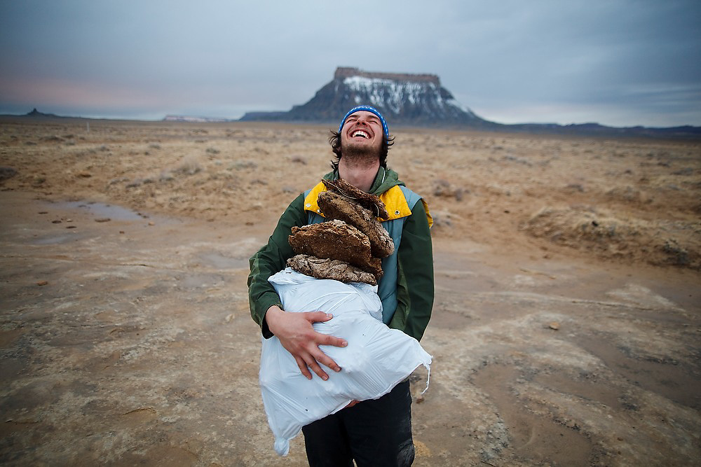University of Colorado geology graduate student Leif Anderson breaks into laughter as he carries a load of dried cow patties he gathered for building a fire to camp on BLM land near Factory Butte, Utah.