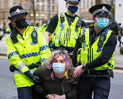 """© Licensed to London News Pictures. 27/03/2021. Manchester, UK. A woman wearing ACAB ( All Coppers Are Bastards ) earrings is carried away . Police move in to remove and detain protesters who were sitting on and blocking tram tracks in St Peter's Square in Manchester City Centre . """" Kill the Bill """" and Reclaim the Streets demonstrations are held in Manchester City Centre in opposition to the Police, Crime, Sentencing and Courts Bill 2021 that is currently before Parliament and after the death of Sarah Everard in London . Photo credit: Joel Goodman/LNP"""