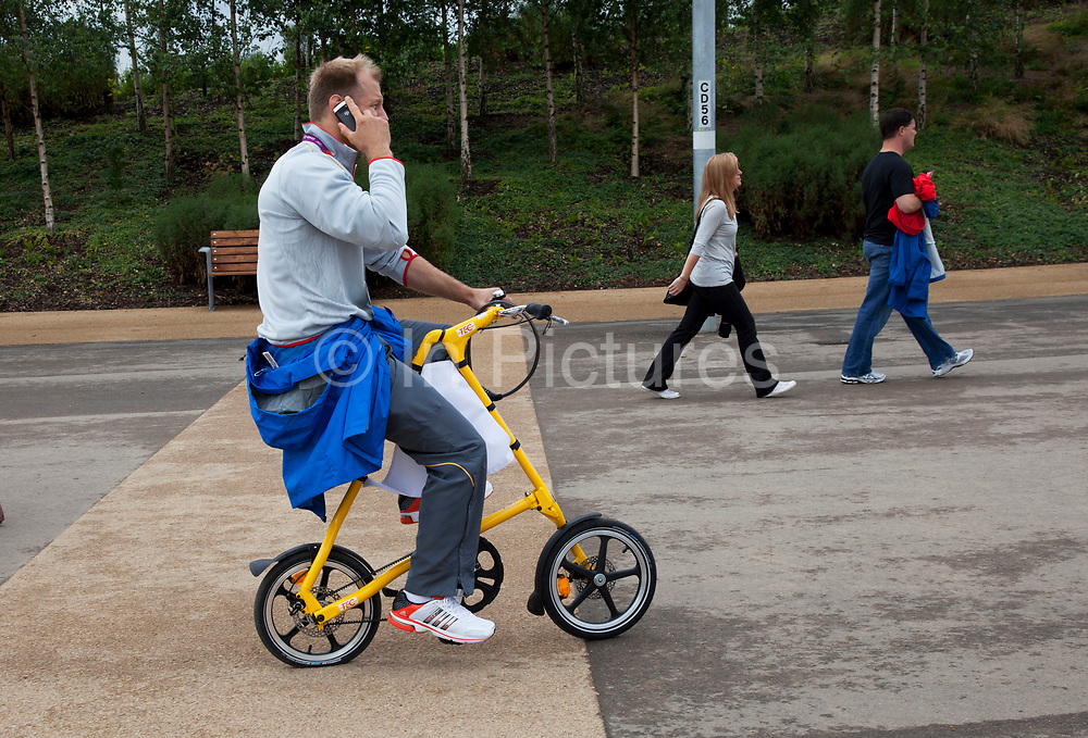 London 2012 Olympic Park in Stratford, East London. Man on his mobile phone gets around the site easily on his compact bicycle.