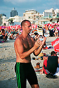 Israel, Tel Aviv, Drums beach a shirtless man juggling a contact ball during a beach party