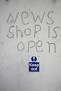 A newsagents shop business is newly open for business but a sticker urges people to stay out in a contradictory message near Angel, north London England.