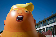 The Trump Baby sitting team give the six metre high inflatable TrumpBaby his first London outing inside the disused North London playground, Islington, London, United Kingdom. 26th June 2018. The plan, is to fly him above Parliament Square in Westminster when the real Trump, president of the United States arrives in the United Kingdom on the 13th of July 2018.