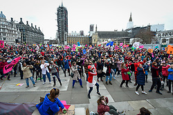 "© Licensed to London News Pictures. 22/02/2020. LONDON, UK.  Activists from Extinction Rebellion take part in an act of 'discobedience', dancing to Saturday Night Fever during ""Enough is enough, Together we march"" in Parliament Square calling for governments to act on the negative effects of climate change.  Photo credit: Stephen Chung/LNP"