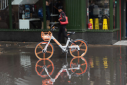 © Licensed to London News Pictures. 01/11/2018. London, UK. People walk past a bike parked in a deep rain puddle after heavy rainfall hit London at lunchtime. Photo<br />  credit: Ray Tang/LNP