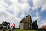 Een man ritst de pijpen van de afritbroek bij het kerkje in Spaarnwoude<br /> <br /> Cyclists during a break in Spaarnwoude