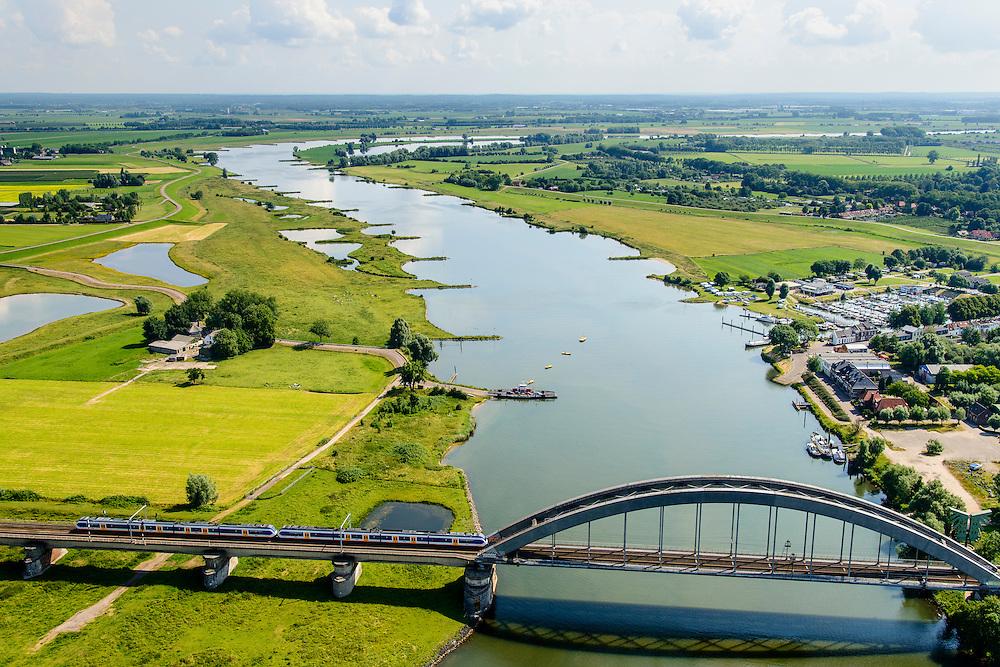 Nederland, Gelderland, Culemborg, 26-06-2014. Rivier de Lek en spoorbrug Culemborg (Kuilenburgse spoorbrug). In de Goilberdingerwaard en Baarsemwaard (links) is de zomerdijk verlaagd en gedeeltelijk weggegraven en ook zijn in de uiterwaard geulen gegraven om rivier de Lek bij hoogwater meer de ruimte te geven. Railway bridge Culemborg and Lek River. In the floodplains (left) the summer dike has been reduced in height and partially excavated, and trenches haven been dug to create 'room for the river' at heigh waters.<br /> luchtfoto (toeslag op standard tarieven);<br /> aerial photo (additional fee required);<br /> copyright foto/photo Siebe Swart
