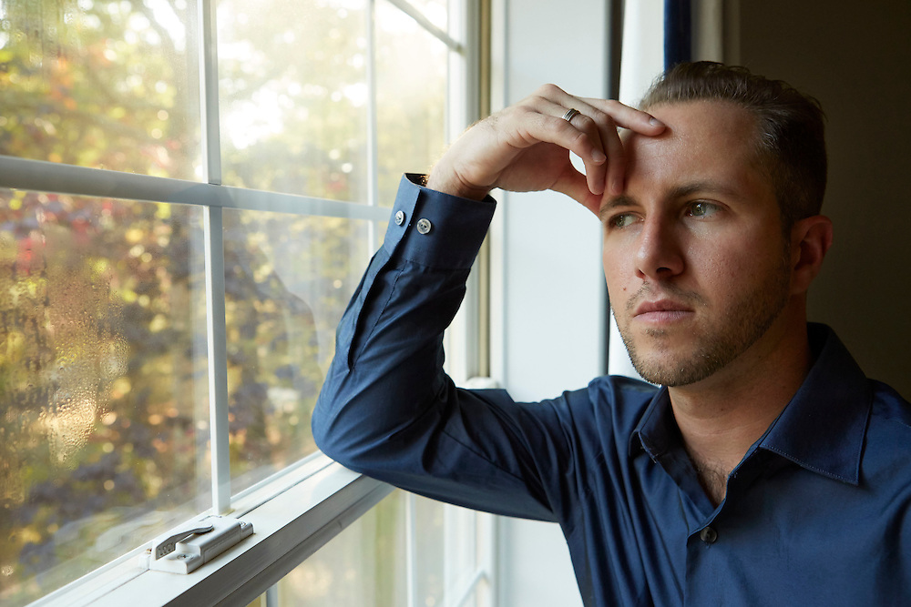 Portrait of a man in shadow, looking out the window, who is in deep thought, worried, anxious, and depressed