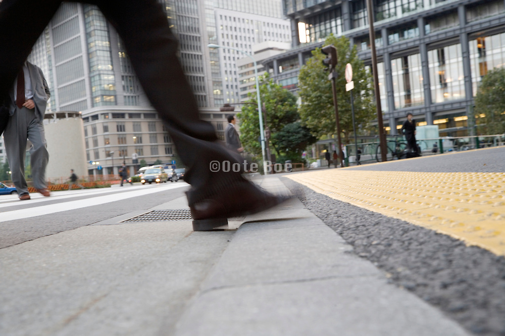 low angel view of businessman stepping of a zebra crossing