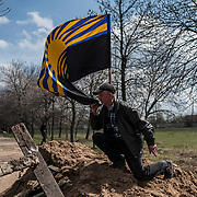 A man kisses the Donbass flag raised outside a military airbase near Kramatorsk.