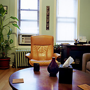 """An orange leather """"Stressless"""" chair against a light green wall and two windows, a large round table in the foreground."""