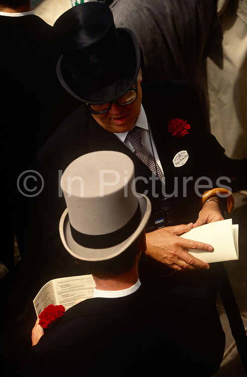 Seen from above, we see top-hatted gents discussing business or racing on Ladies Day at Royal Ascot racing week. From our aerial perspective we see their suits and carnation button-holes and racing cards on which details of runners and riders are listed. The name of Major Michael Young is on one man's name badge. Royal Ascot is held every June and is one of the main dates on the sporting calendar and English social season. Over 300,000 people make the annual visit to Berkshire during Royal Ascot week, making this Europe's best-attended race meeting. There are sixteen group races on offer, with at least one Group One event on each of the five days. The Gold Cup is on Ladies' Day on the Thursday. There is over £3 million of prize money on offer.
