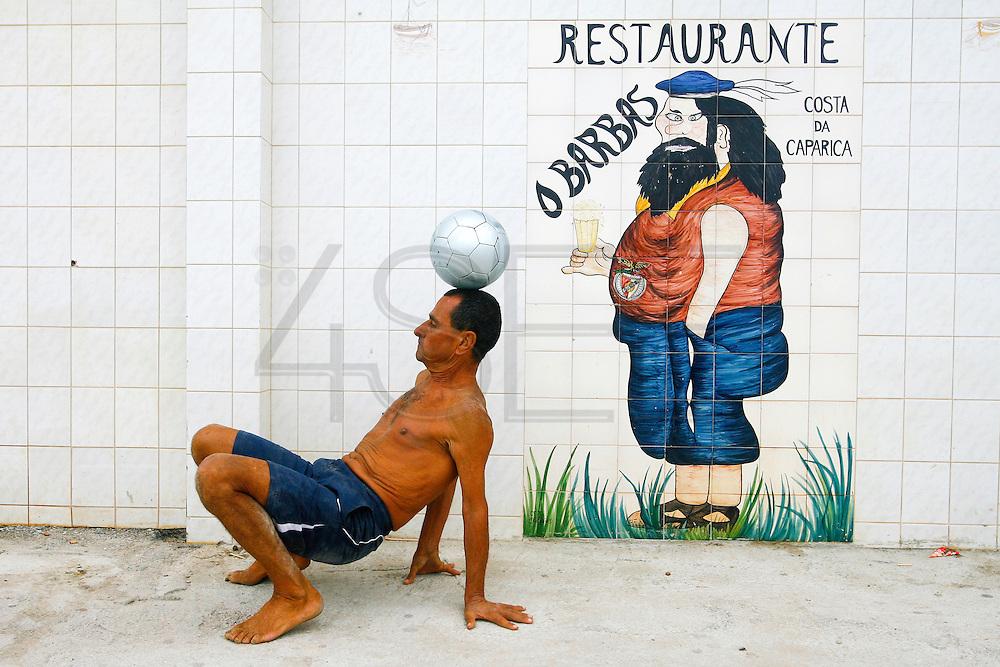"Portuguese Summer. A man plays with his ball near the known restaurant ""O Barbas""  at the Costa da Caparica beach."