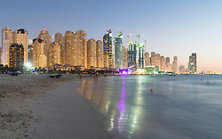 Night view of beach and skyline of high-rise apartment blocks at JBR Jumeirah Beach Residences in Dubai UAE