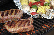KEVIN BARTRAM/The Daily News.Steaks and vegetables on the grill make a good summertime meal.
