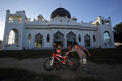 Adi,in front with his friends Syakir at back 9 yrs and Haikal with his bike at Rahmatullah Mosque in Lampuuk village,  which was heavily damaged in the Indian Ocean Tsunami in Dec 2004. District Aceh Besar, Aceh Province, Sumatra, Indonesia