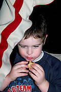 Israel, Jordan Valley, Kibbutz Ashdot Yaacov, Eating Sufganyot during a Hanukah celebration
