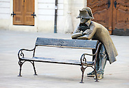 Statue of Napoleonic soldier leaning on bench, one of several humorous statues which grace the streets of the Slovak capital, in the Main Square (Hlavne namestie), Bratislava, Slovakia