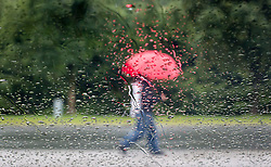 THEMENBILD - Spaziergänger mit Regenschirm, durch eine mit Regentropfen benetzte Scheibe eines PKWs fotografiert, aufgenommen am 12.08.2014 in Kaprun, Österreich // two People carrying an umbrella, photographed from behind a window, covered with rain drops during rainy weather in Kaprun, Austria on 2014/08/12. EXPA Pictures © 2014, PhotoCredit: EXPA/ JFK