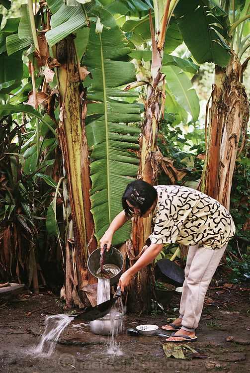 Buaphet Khuenkaew, 35, rinses the pans and dishes she has just washed in the backyard of her house, under a banana tree. The Khuenkaew family lives in a wooden 728-square-foot house on stilts, surrounded by rice fields in the Ban Muang Wa village, outside the northern town of Chiang Mai, in Thailand. Material World Project.