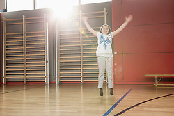 Cheerful small girl jumping in sports hall, Munich, Bavaria, Germany