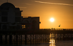 © Licensed to London News Pictures. 30/10/2017. Southsea, UK.  Two anglers fishing on Southsea pier as the sun rises into the clear sky this morning, 30th October 2017. Photo credit: Rob Arnold/LNP
