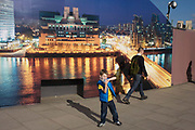 "A young boy plays by a construction hoarding, a night time panorama of the Thames south bank, featuring the HQ of the intelligence service (MI6) across the river in Vauxhall. Under the gaze of a CCTV camera, the lad plays a fantasy game with his plastic water bottle as a stranger strides on towards a local station. The temporary hoarding will stay in place for the time that the company's new residential riverfront apartments are under construction. In the image, the building at Vauxhall Cross, is located at 85 Albert Embankment beside Vauxhall Bridge. It is known within the intelligence community as ""Legoland"" and ""Babylon-on-Thames""."