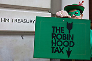 On the day before Alistair Darling makes his 2010 Budget speech, around a dozen Robin Hoods delivered their own green Budget boxes to the Treasury, calling on the Chancellor to announce the introduction of a tax on banks' financial transactions. Robin Hoods marched from College Green across Parliament Square en route to the Treasury offices. Inside the green boxes will be a letter to the Chancellor calling on him to kick start international agreement for new financial transaction taxes by announcing a new unilateral UK sterling tax. The boxes also contain info reminding of the support that the Robin Hood Tax campaign has gathered since it launched last month. Some 100 organisations are now backing the coalition, which has 141,085 fans on Facebook and 71,492 people have voted yes to a financial transactions tax on the campaign's website www.robinhoodtax.org.uk