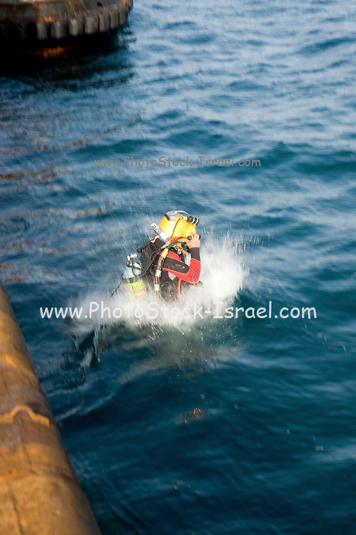 Commercial diver entering the Mediterranean sea. Cables from the surface are supplying electrical power for the lights, and allowing communication with the surface. The diver is using a helmet connected to an air supply on his back. Photographed of the shore of Hadera, Israel