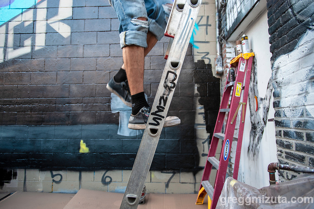 """Jacob Coe on the ladder working on his collaborative """"Bones Brothers Collective"""" mural during Freak Alley Gallery's eighth annual mural event in downtown Boise, Idaho on August 6, 2018. <br /> <br /> The mural was a collaboration between brothers Jacob Coe and Taylor Coe. They are the founders of the Bones Brothers, a collective of progressive people in Boise Idaho. A Bones Brother is someone who adventures, someone who is positive, someone who is passionate at things that drive them, someone who on a whim will jump into something.<br />  <br /> Freak Alley Gallery's week long event provided an """"art-in-motion"""" experience as it welcomed the public to watch artists work on their murals."""