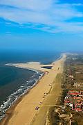 Nederland, Zuid-Holland, Gemeente Westland, 23-05-2011; Onder in beeld nieuw aangelegde duinen ter hoogte van Ter Heijde. De verbrede duinen liggen op de plaats van wat vroeger een van de Zwakke Schakels van de Kust was.Op het tweede plan de Zandmotor, aanleg van kunstmatig schiereiland door het opspuiten van zand voor de kust. Wind, golven en stroming zullen het zand langs de kust verspreiden waardoor breder stranden en duinen ontstaan. De zandmotor is een experiment in het kader van kustonderhoud en kustverdediging. In de achtergrond de kassen van het Westland..Sand Engine, construction of artificial peninsula by the raising of sand for the coast of Ter Heijde (near the Hague). Wind, waves and currents will distribute the sand along the coast yielding wider beaches and dunes along the coastline. The Sand Engine is a experiment for coastal maintenance of coastal defense. In the background the Westland greenhouses..luchtfoto (toeslag); aerial photo (additional fee required).foto Siebe Swart / photo Siebe Swart