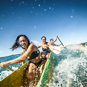 Outrigger canoe surfing in A Bay on the Big Island of Hawaii.
