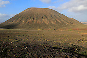 Volcanic cone with, to the left, Miguel de Unamuno monument, Tindaya, Fuerteventura, Canary Islands, Spain