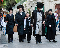 © Licensed to London News Pictures. 02/05/2014. Jerusalem, Israel. Jewish families hurry through the Muslim Quarter of the Old City of Jerusalem at approx 6.30pm in order to reach The Western Wall  in time for the start of the Shabbat (the Jewish sabbath).  Jewish custom sees the lighting of candles scheduled for 6.39pm this evening, shortly before the sunset when Shabbat commences.  The Western Wall is the most important shrine of the Jewish faith and is located in the Old City at the foot of the western side of Temple Mount. The Old City is comprised of four Quarters - the Jewish, Muslim, Christian and Armenian.  Photo credit : Richard Isaac/LNP