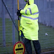 Storm Gertrude.  A lollipop man braces himself against the school fence at Cranhill Primary School in Glasgow. Picture Robert Perry 29th Jan 2016<br /> <br /> Must credit photo to Robert Perry<br /> FEE PAYABLE FOR REPRO USE<br /> FEE PAYABLE FOR ALL INTERNET USE<br /> www.robertperry.co.uk<br /> NB -This image is not to be distributed without the prior consent of the copyright holder.<br /> in using this image you agree to abide by terms and conditions as stated in this caption.<br /> All monies payable to Robert Perry<br /> <br /> (PLEASE DO NOT REMOVE THIS CAPTION)<br /> This image is intended for Editorial use (e.g. news). Any commercial or promotional use requires additional clearance. <br /> Copyright 2014 All rights protected.<br /> first use only<br /> contact details<br /> Robert Perry     <br /> 07702 631 477<br /> robertperryphotos@gmail.com<br /> no internet usage without prior consent.         <br /> Robert Perry reserves the right to pursue unauthorised use of this image . If you violate my intellectual property you may be liable for  damages, loss of income, and profits you derive from the use of this image.
