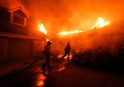 Firefighters battle the Woolsey fire burning a home in Malibu, Calif., Friday, Nov. 9, 2018. The Woolsey Fire was a destructive wildfire that burned in Los Angeles and Ventura Counties of the U.S. state of California. The fire ignited on November 8, 2018 and burned 96,949 acres of land.