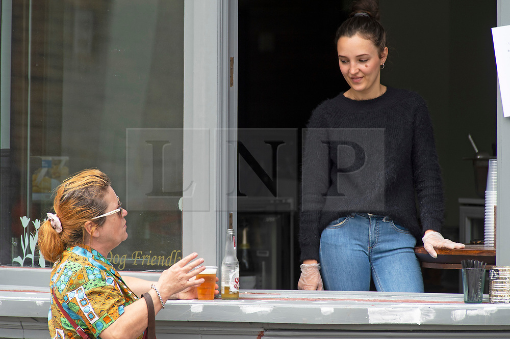 ©Licensed to London News Pictures 15/06/2020<br /> Greenwich, UK. A lady having a beer at the Greenwich Tavern pub window bar. People out and about in Greenwich park, Greenwich, London enjoying the warm sunny weather and Coronavirus lockdown freedom. Photo credit: Grant Falvey/LNP