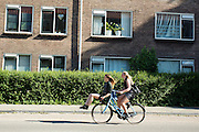 In Utrecht fietst een meisje met een meisje voorop de drager.<br /> <br /> In Utrecht a girl cycles with a girl on the front carrier.