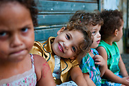 Sidon, Lebanon - September 24, 2010: Faces of children, including a beautiful smiling girl, sitting in their neighborhood in the old city of Sidon, Lebanon.