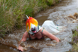 © Licensed to London News Pictures. 30/08/2015. Llanwrtyd Wells, Powys, Wales, UK. Two participants dress as a unicorn. World Bogsnorkelling Championships, conceived 30 years ago in a Welsh pub by landlord Gordon Green, are held every August Bank Holiday at Waen Rhydd Bog. Using unconventional swimming strokes, participants swim two lengths of a 55 metre trench cut through a peat bog wearing snorkel and flippers. The world record was broken in 2014 by 33 year old Kirsty Johnson from Lightwater, Surrey, in a time of 1 min 22.56 secs. Photo credit: Graham M. Lawrence/LNP