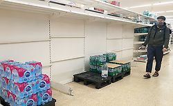 © Licensed to London News Pictures. 30/07/2021. London, UK. A shopper wearing a face covering walks past nearly-empty shelves of bottled drink water in Sainsbury's, north London. Record breaking numbers of people have been forced to self-isolate after being alerted by the NHS Covid-19 app. The pingdemic has seen staff shortages at supermarkets, resulting in less stock making its way to supermarket shelves. Labour leader Sir Keir Starmer has demanded that the government brings forward the end to self-isolation from 16 August to 7 August. Photo credit: Dinendra Haria/LNP