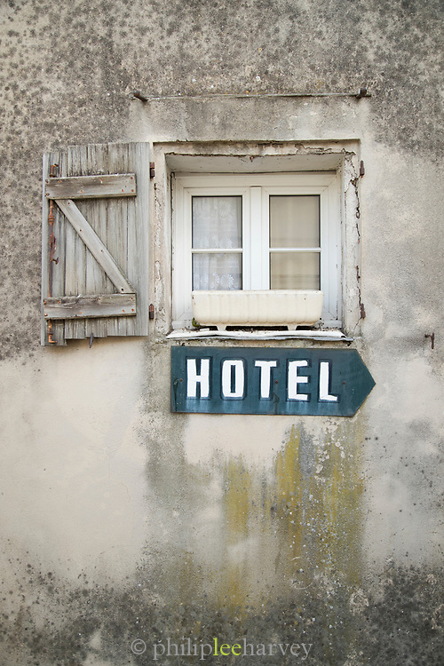 Old hotel sign under old wooden window with shutter on dilapidated building facade, Grasse, France